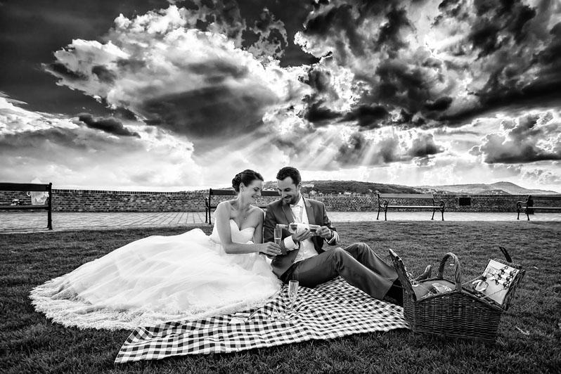 Az ifjú pár egy kis piknikes hangulatban koccint a mezőn, felettünk szép felhőmintázatok.